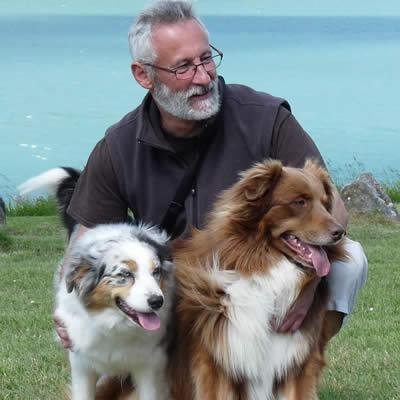 laurent loizzo devant un lac avec deux bergers australiens